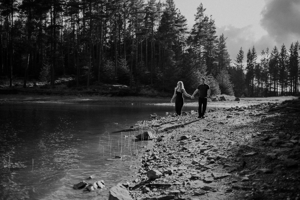 Black and white photo of engaged couple walking along waters edge at Kielder