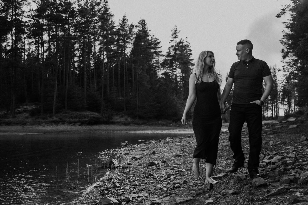 Black and white photo of couple holding hands while walking near Kielder Water