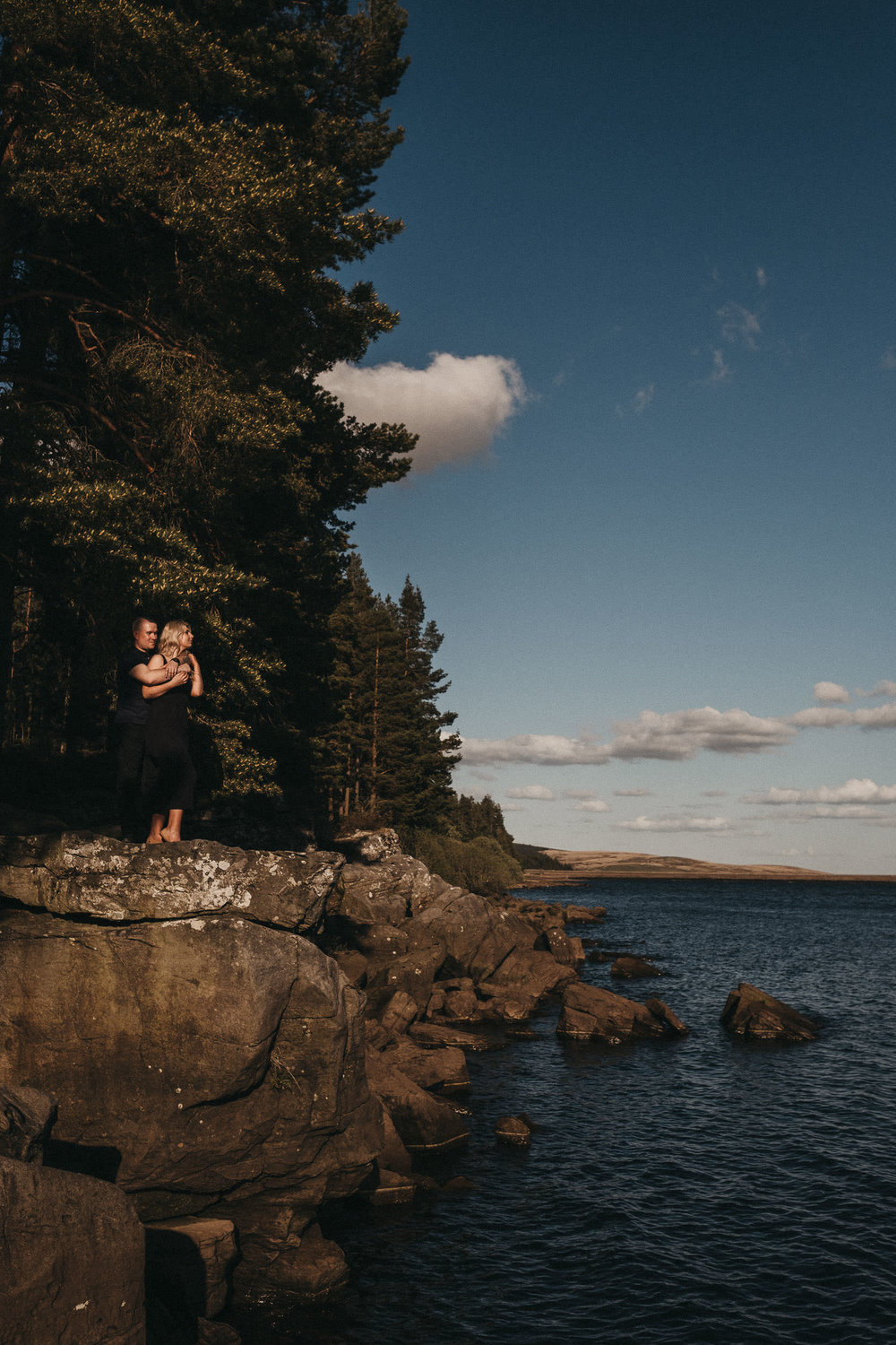 Engaged couple standing on rock above water with trees behind