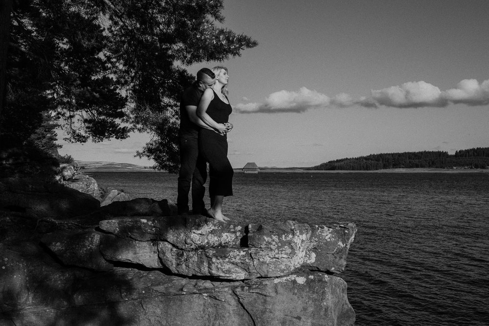 Black and white photo of couple standing on rock overlooking Kielder Water