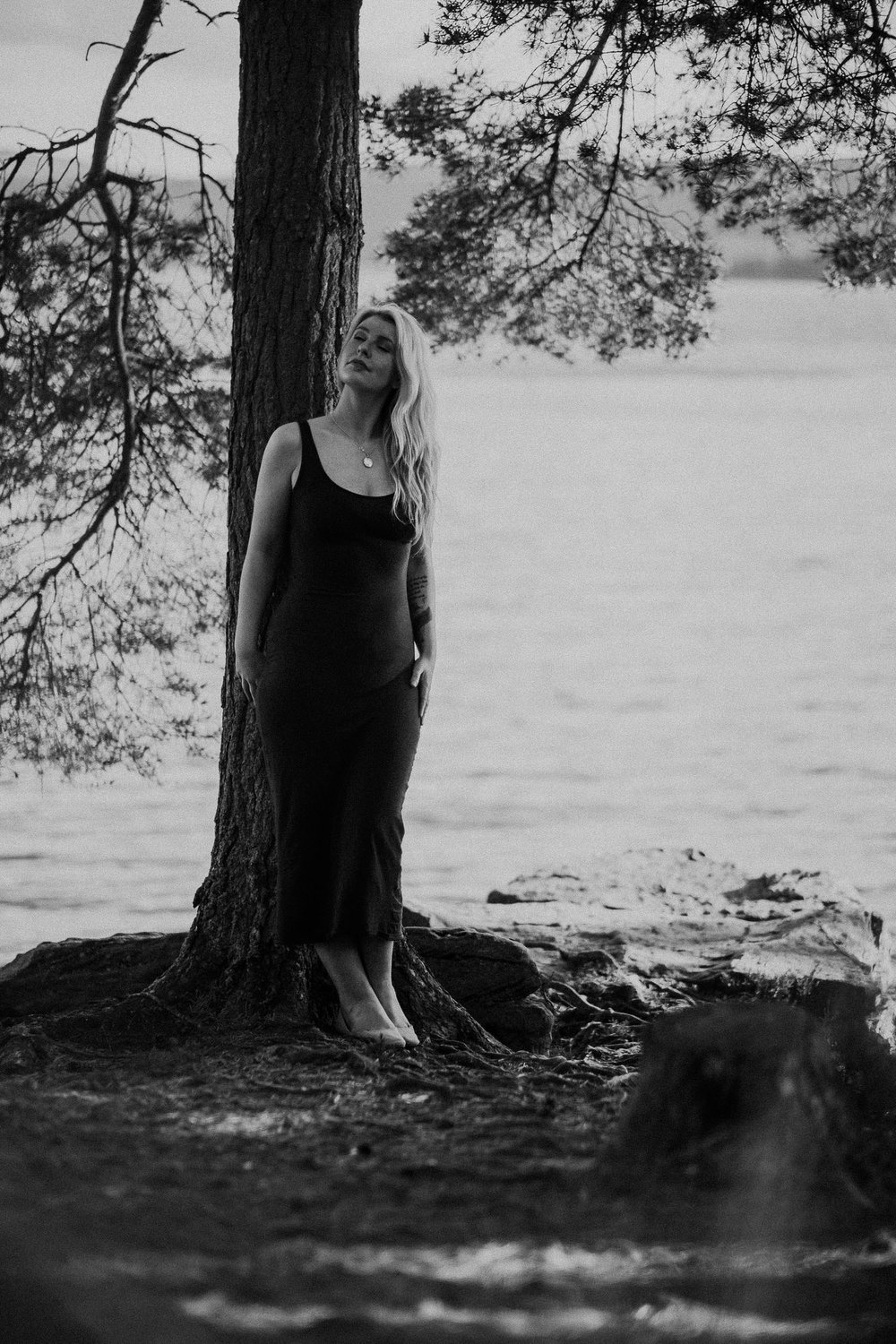 Black and white photo of woman leaning against a tree with her eyes shut