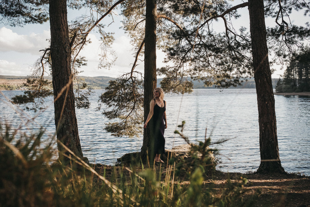 Woman wearing black dress leans against a tree with Kiedler Water in the background
