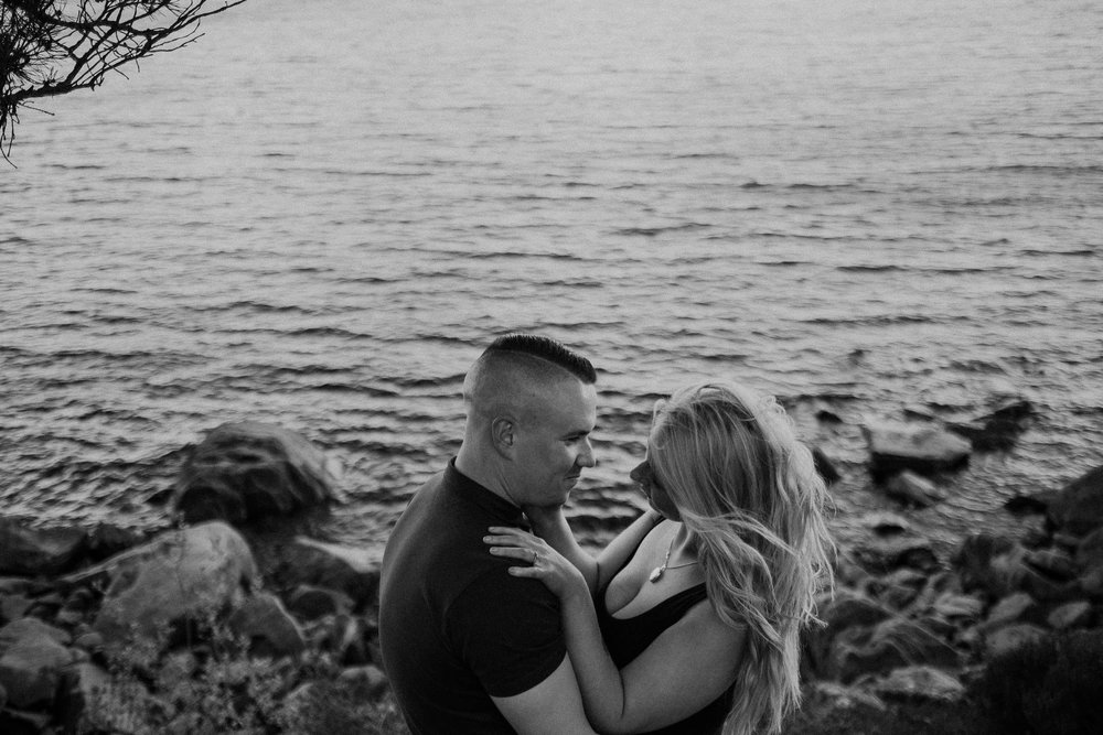 Black and white photo of couple looking into each other's eyes with water in background