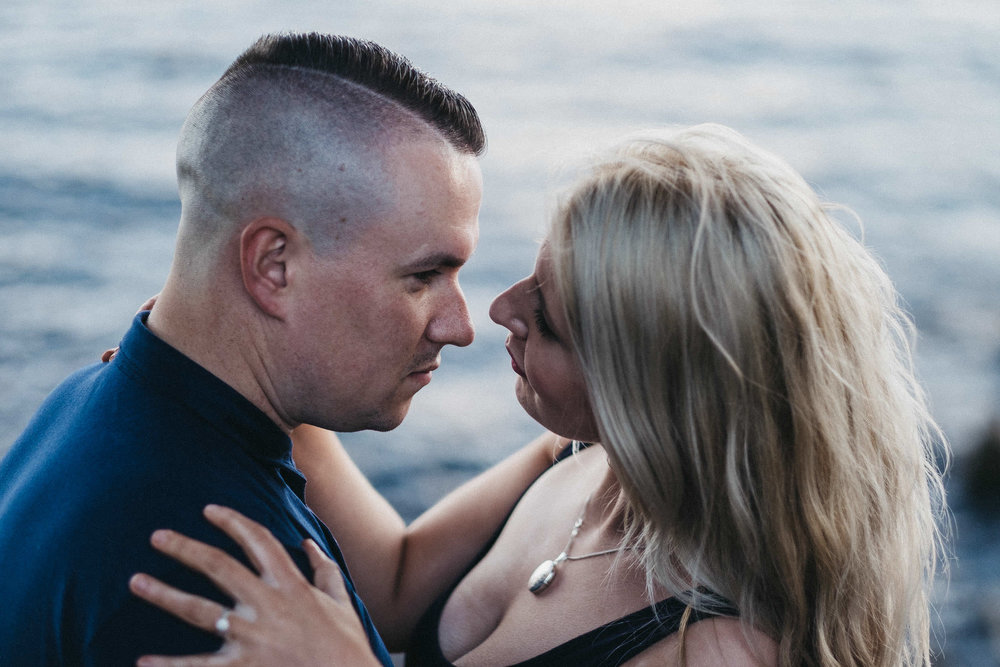 Close up of engaged couple kissing with Kielder Water behind
