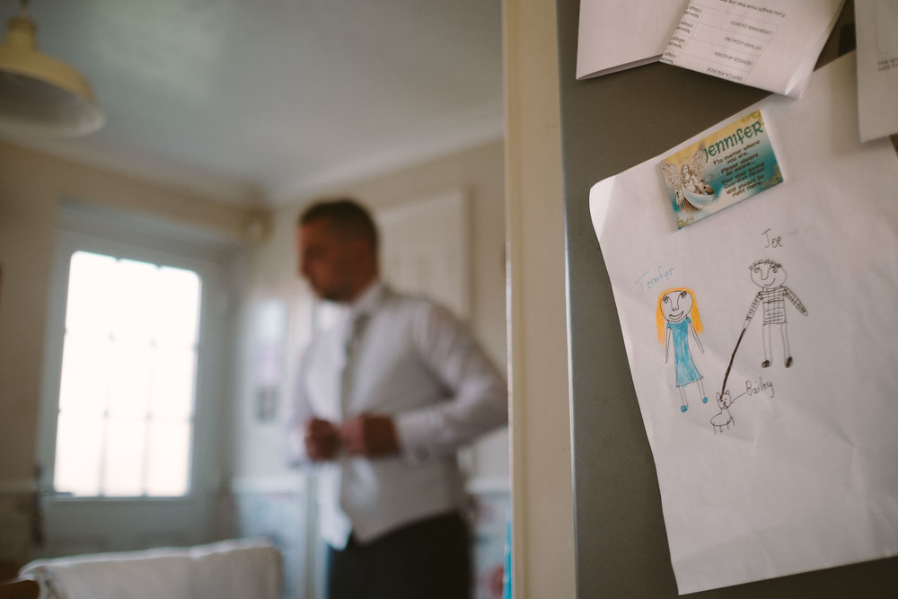 Close up of childs drawing while groom gets ready in background