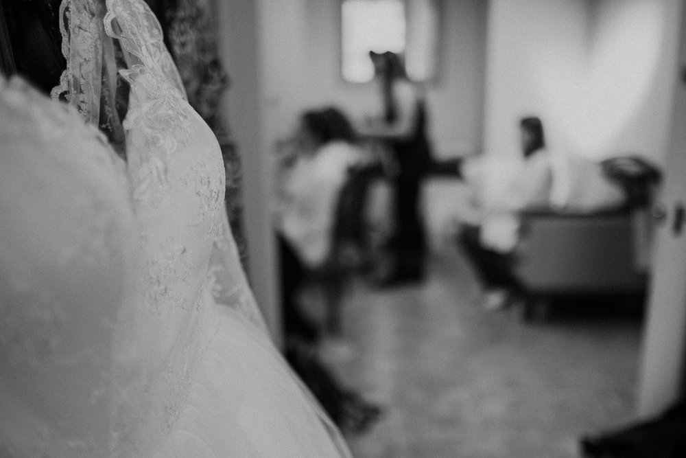 Black and white photo of wedding dress with bride getting ready in the background