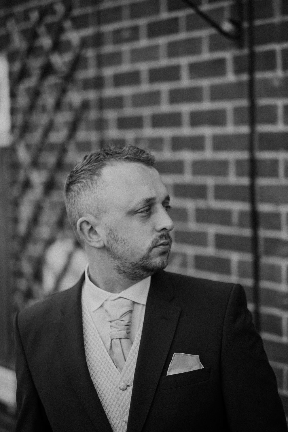 Black and white photo of groom outside home before ceremony