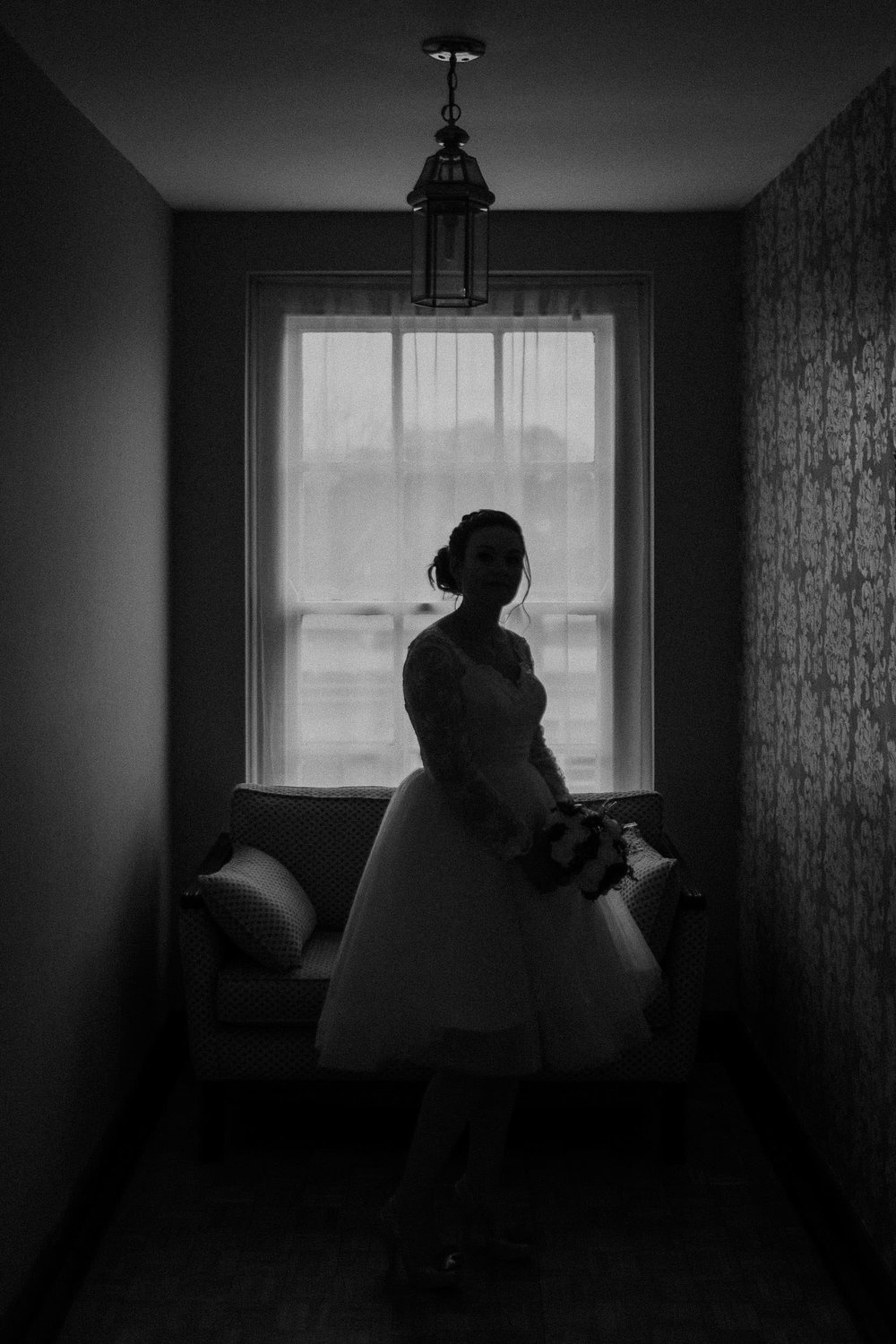 Black and white silhouette photo of bride before ceremony