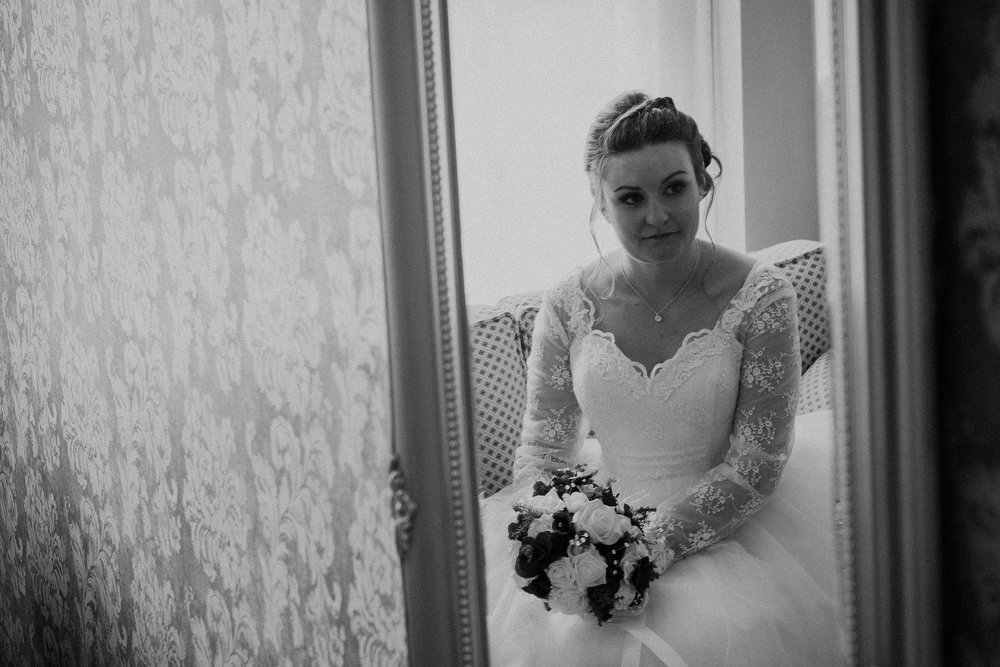 Black and white photo of pensive bride reflected in mirror