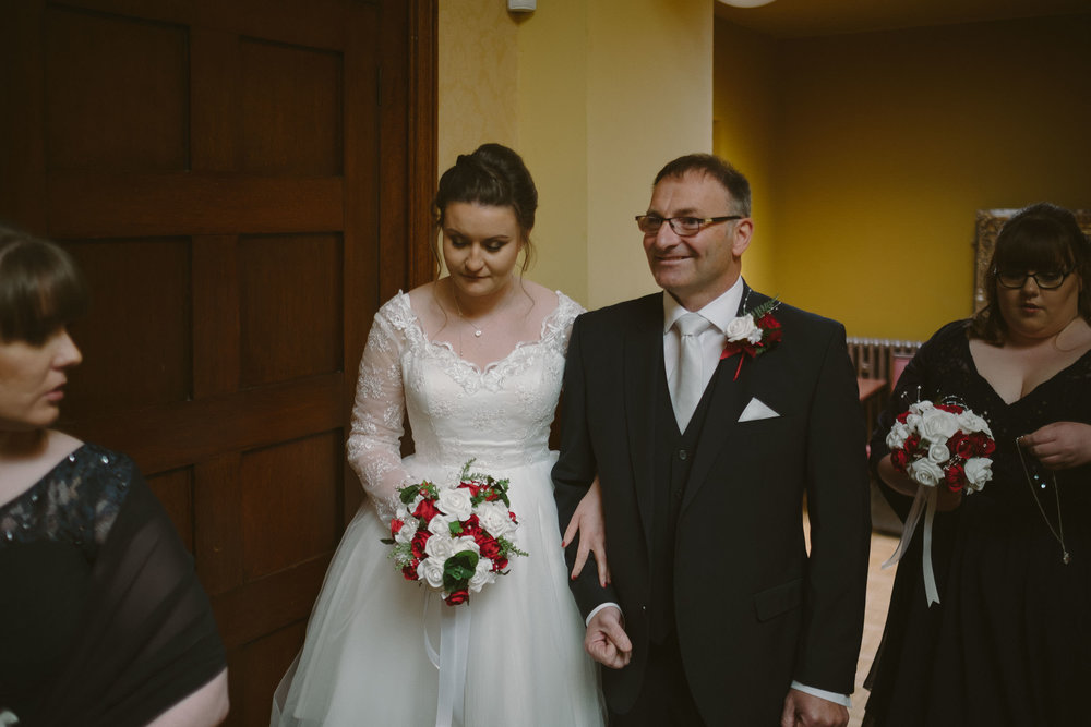 Father of the bride smiling just before he walks his daughter down the aisle