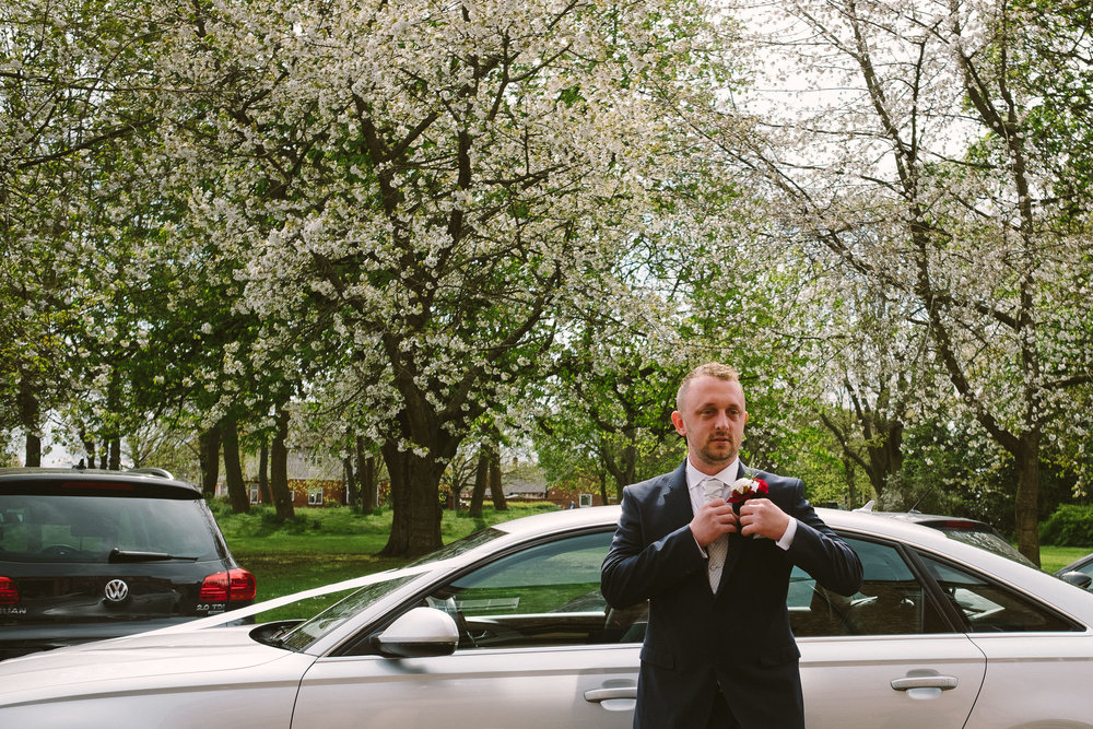 Groom adjusting buttonhole as he arrives at Wallsend Hall
