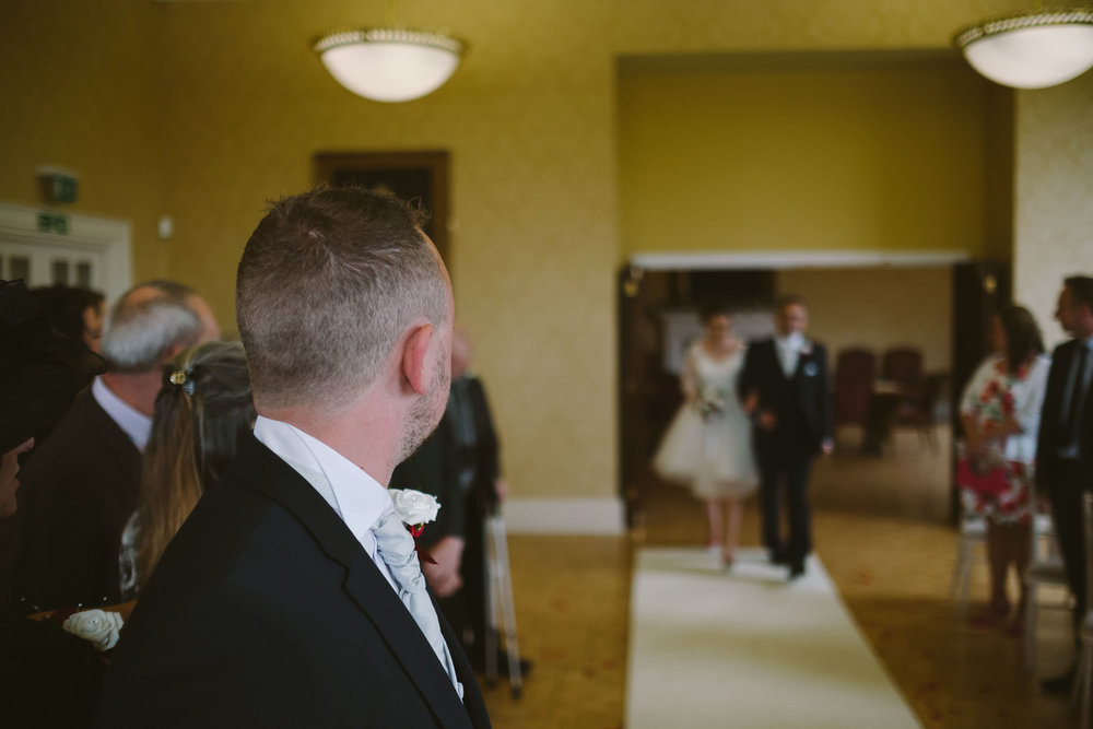 Groom watching bride's entrance to wedding ceremony