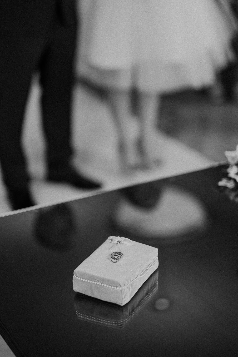 Black and white photo of wedding rings during ceremony with bride and groom behind