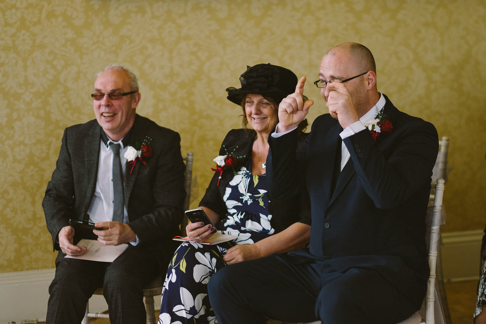 Wedding guest mimes taking a photograph