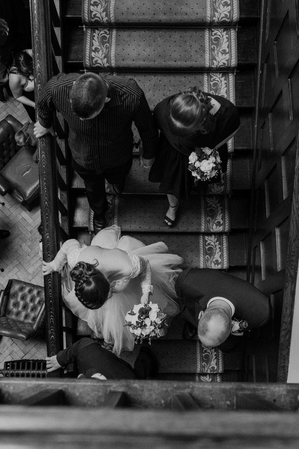 Black and white photo from above of bride and groom walking down stairs