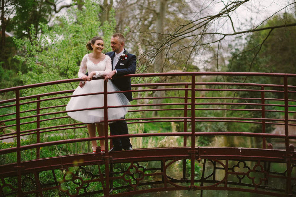 Bride and groom standing on bridge with tree branches in background