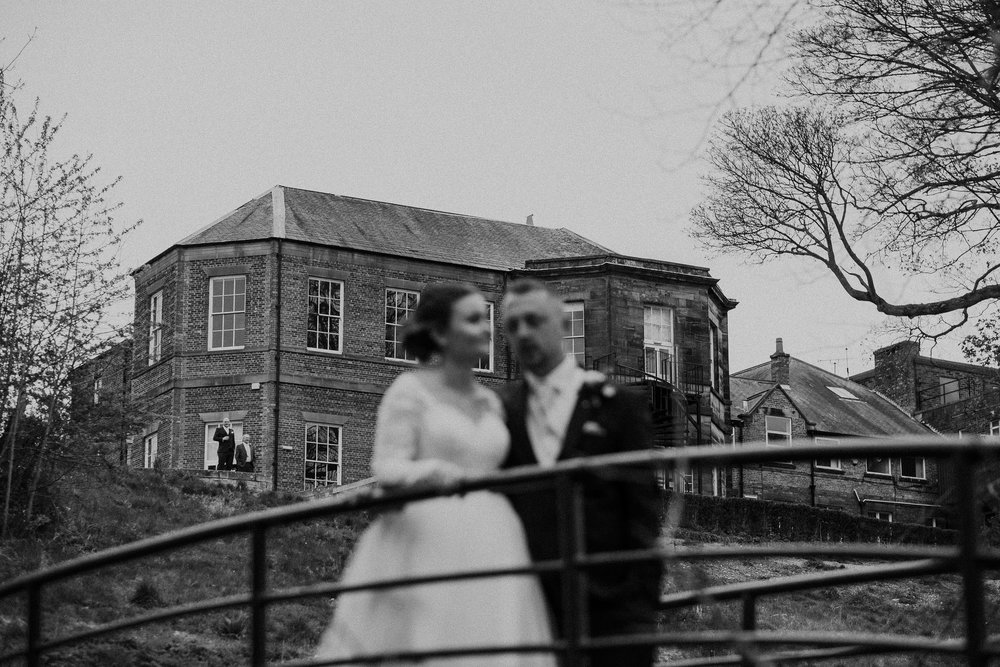 Black and white photo of guests cheering at bride and groom