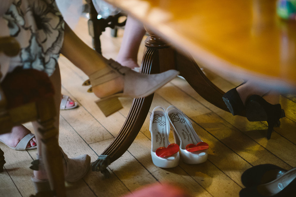 Close up of bride's wedding shoes under table
