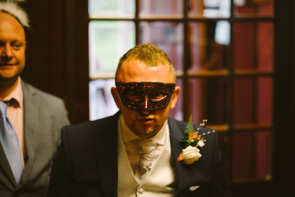 Groom dressed in mask pulling face for camera