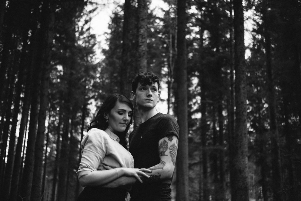 Black and white photo of couple cuddling with tall trees in the background