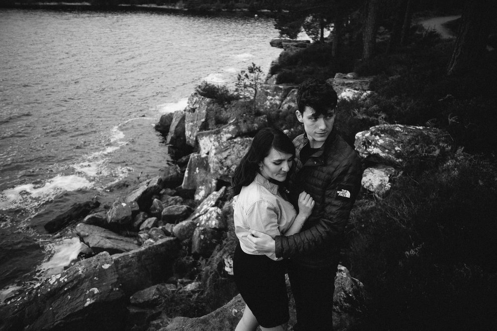 Black and white photo of couple holding each other tight on rocks above Kielder Water