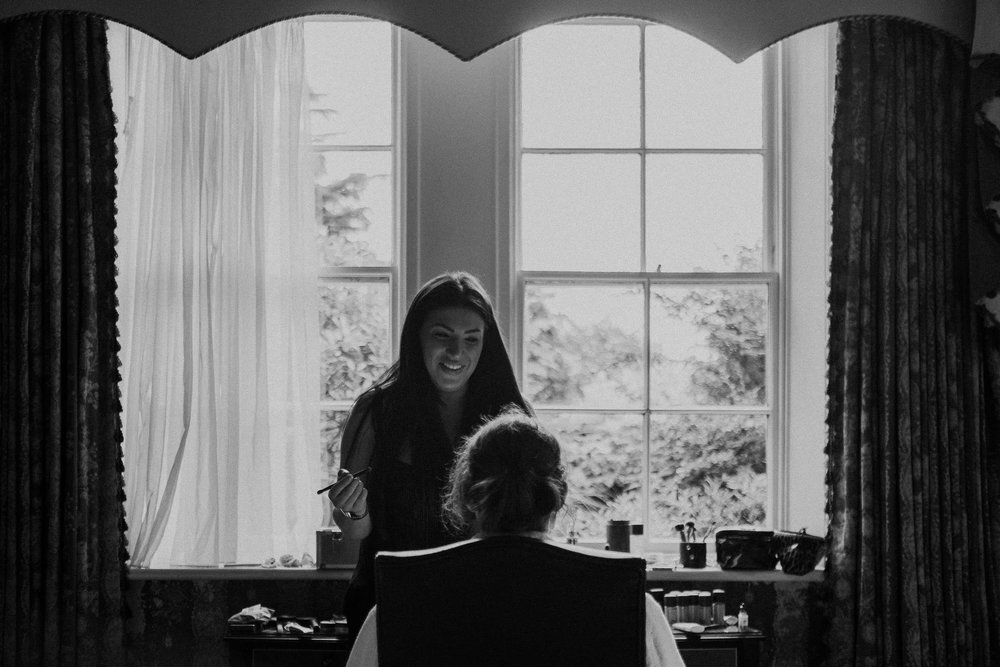 Black and white photo of bride having makeup applied in front of window
