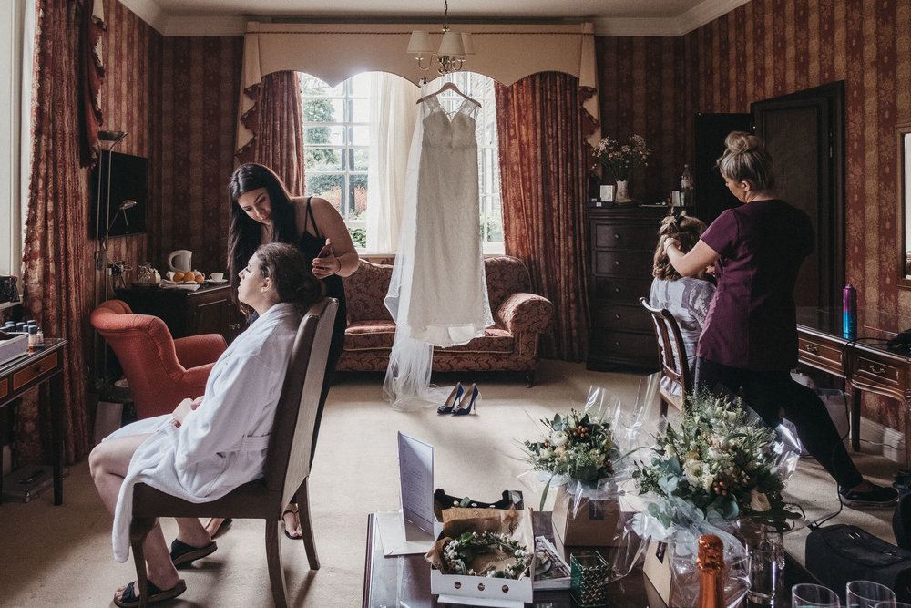 Bride having makeup applied with wedding dress hanging behind