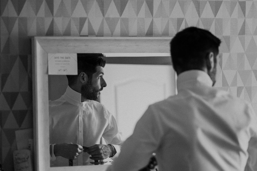 Black and white photo of groom reflected in mirror