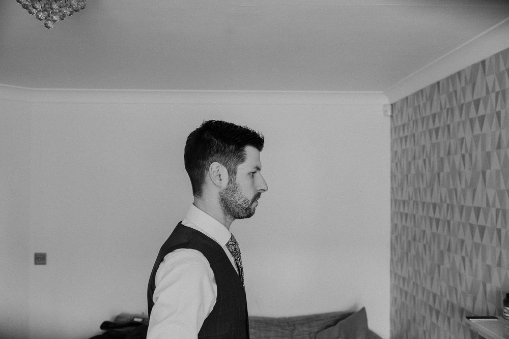 Black and white photo of groom from the side