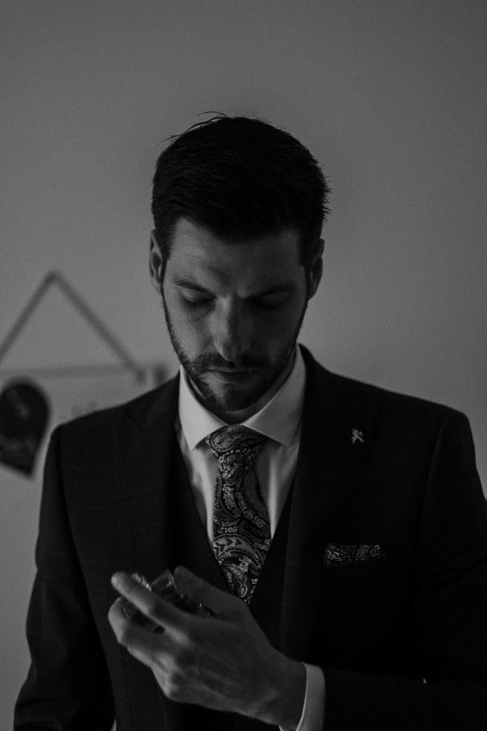 Moody black and white photo of groom getting ready