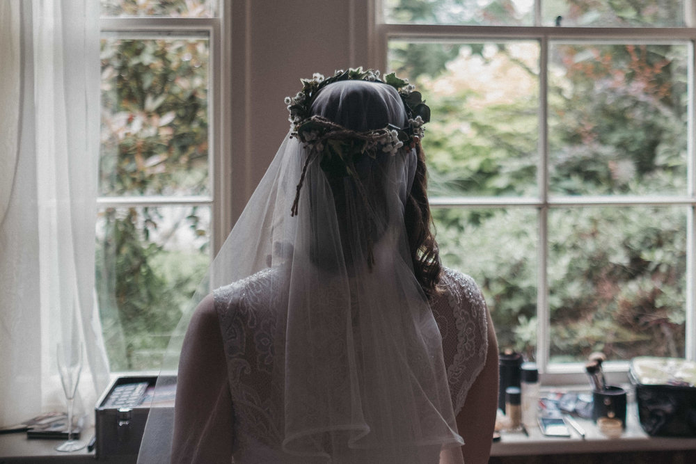 Bride with flower crown looking out of window