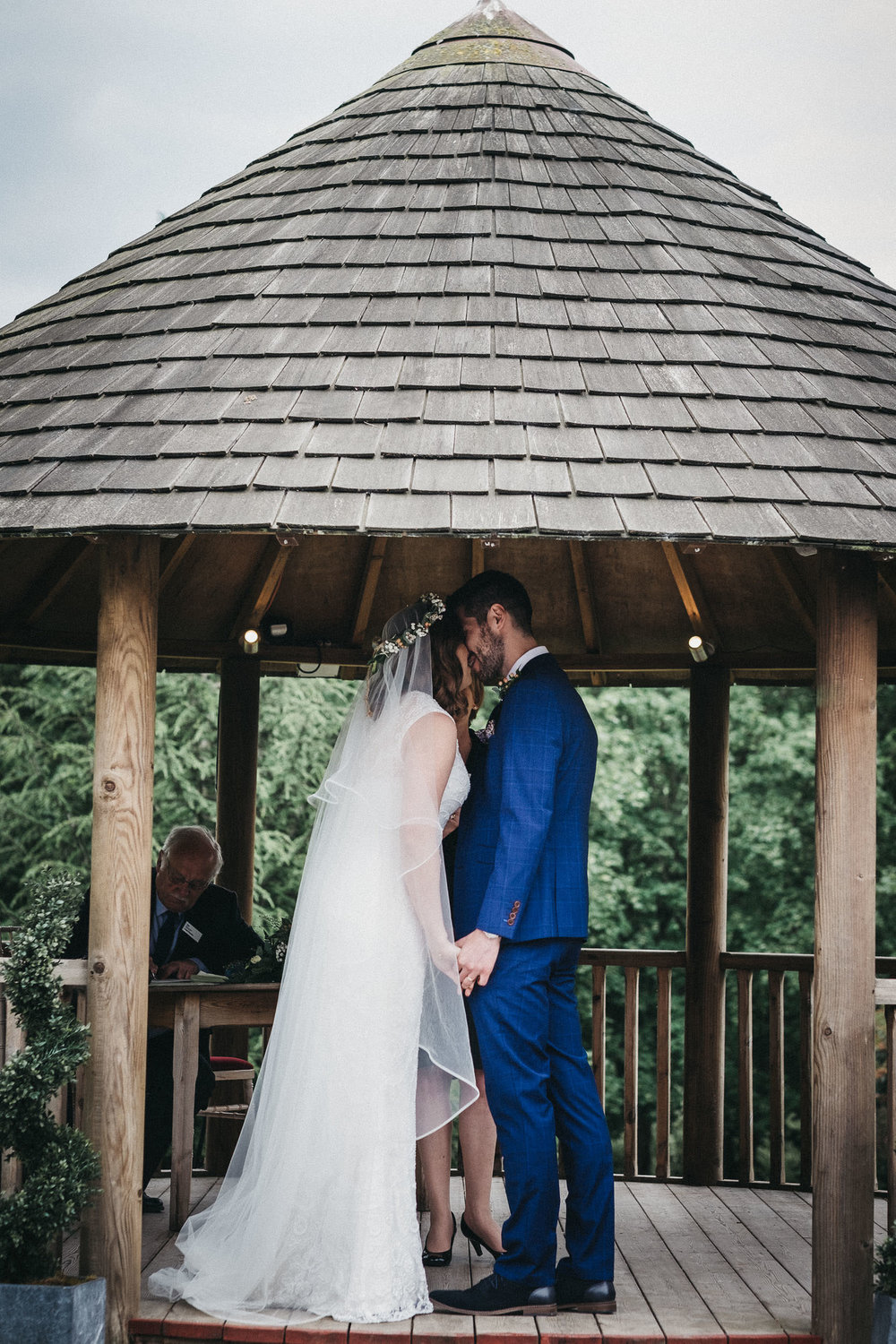 Bride and groom kiss in gazebo during wedding ceremony