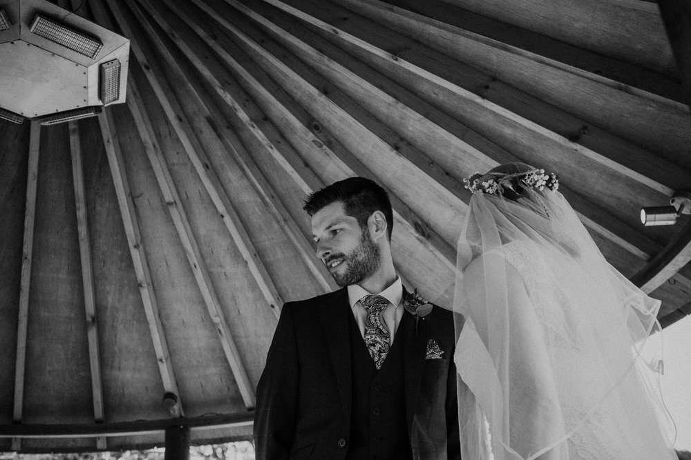 Black and white photo of groom under gazebo roof