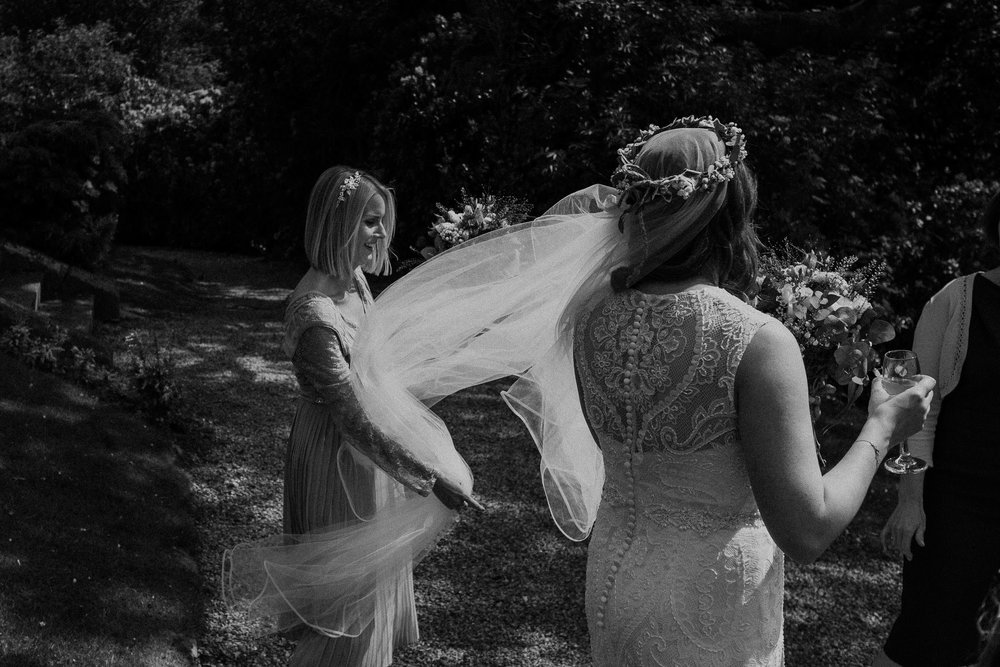 Black and white photo of bridesmaid holding bride's veil in wind
