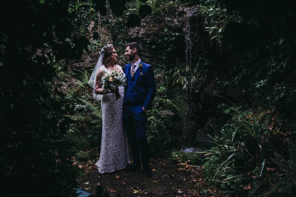 Moody photo of bride and groom with waterfall