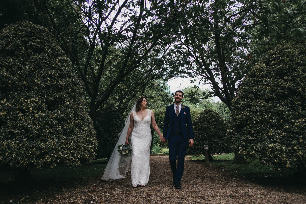 Bride and groom smiling while walking through avenue of trees