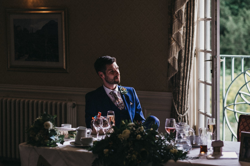 Moody photo of groom watching wedding speeches