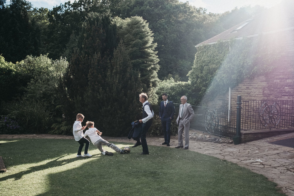 Wedding guests play football in blazing sunlight