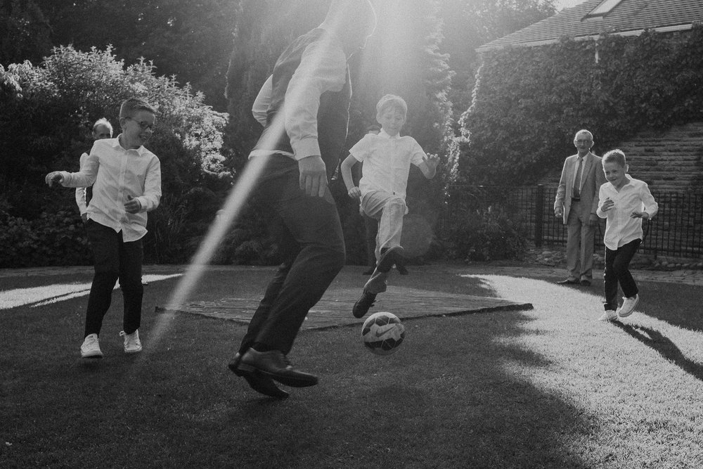 Black and white photo of wedding guests playing football in strong sunlight