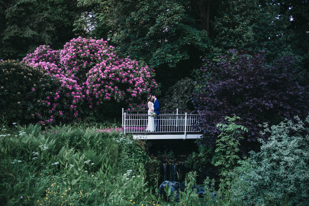 Bride and groom kiss on bridge with pink flowers behind