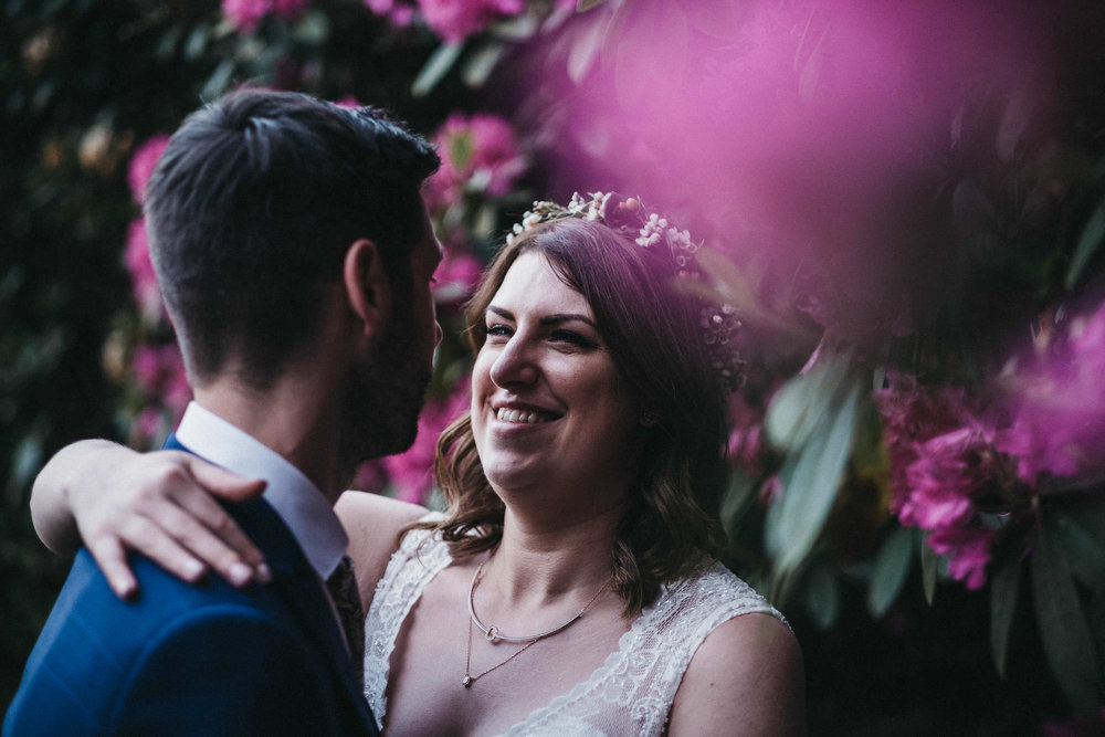 Bride smiles at groom amongst pink flowers