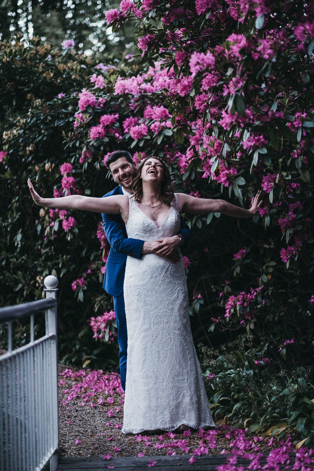 Bride and groom laughing with pink flowers in background