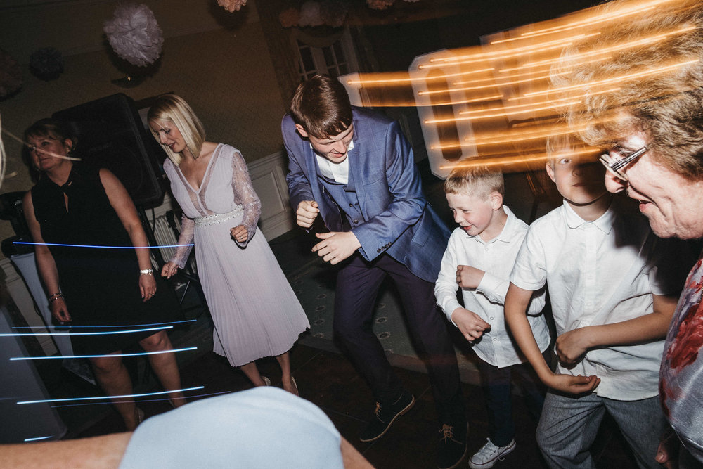 Page boys and guests dancing at wedding