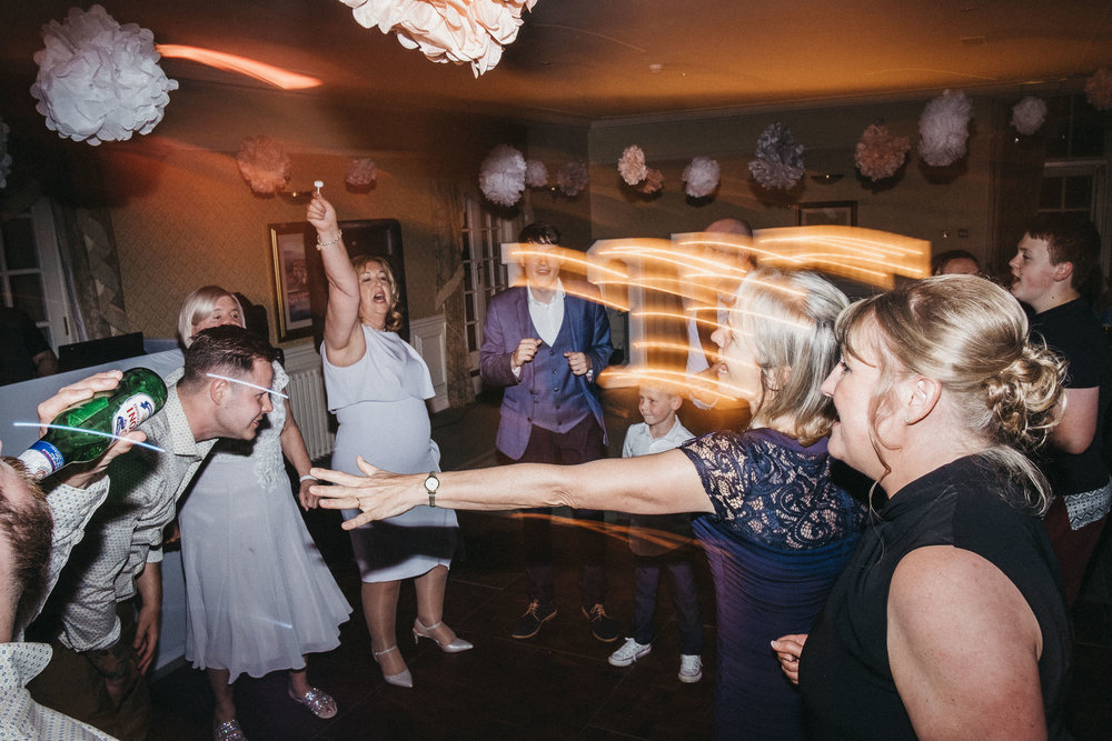 Wedding guests dancing energetically at wedding