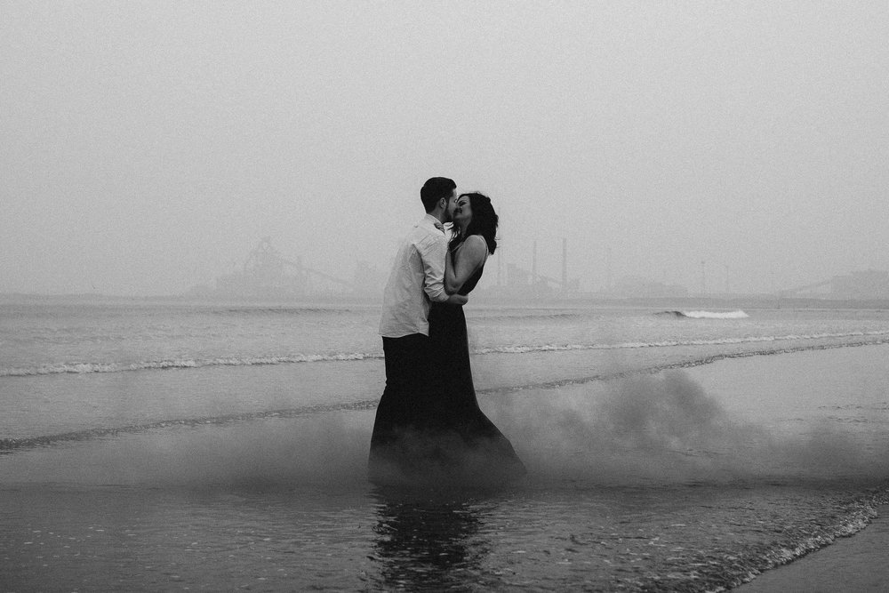 Black and white photo of couple kissing in the sea with smoke curling around them