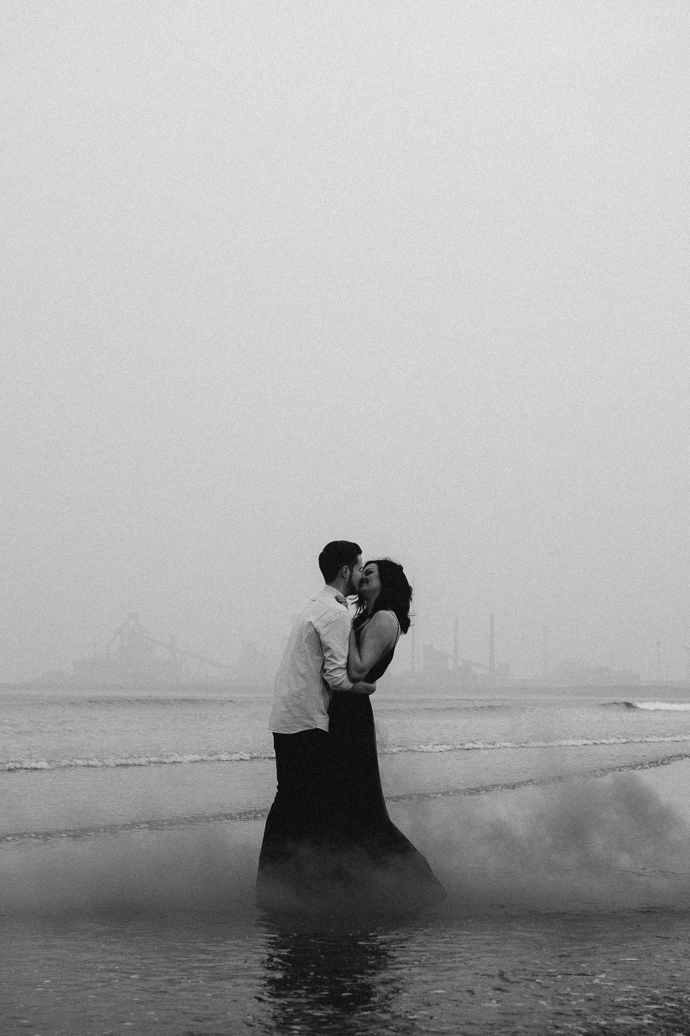 Black and white photo of engaged couple kissing passionately in the sea