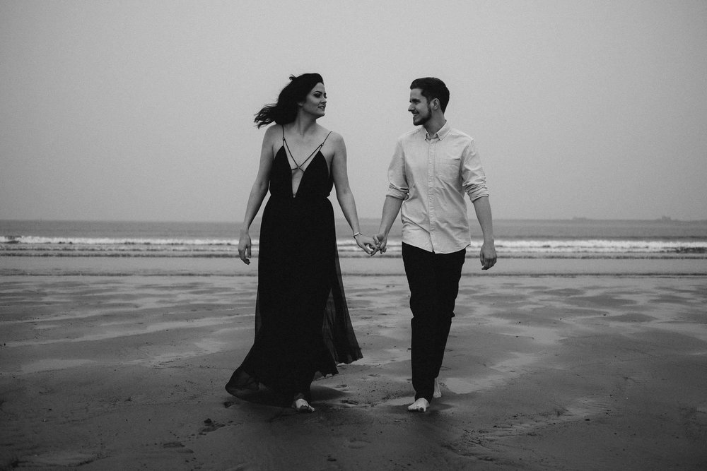 Black and white photo of couple walking up beach holding hands looking at each other