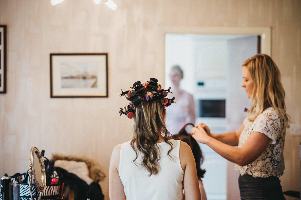 Bride with colourful curlers in hair