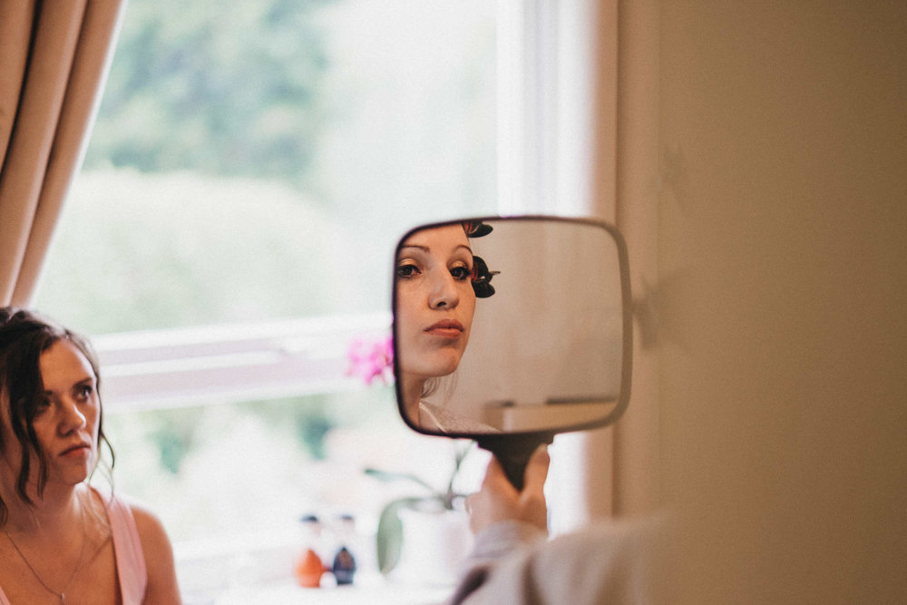 Partial reflection of bride's face in mirror