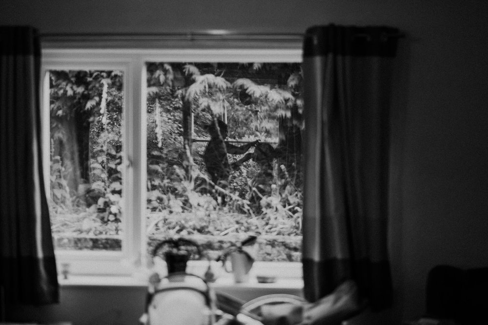 Black and white photo of bride putting on makeup reflected in window